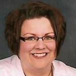 Portrait of woman with short dark hair wearing glasses ans a white shirt.