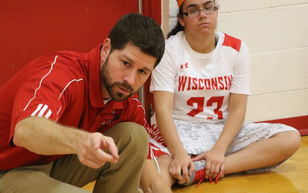 Male basketball coach pointing toward the camera with female player in the background.