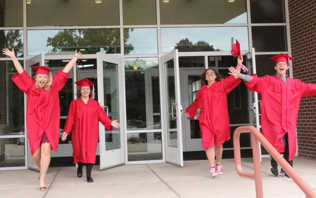 Three female and one male student wearing red graduation caps and gowns, exiting the school building in celebration.