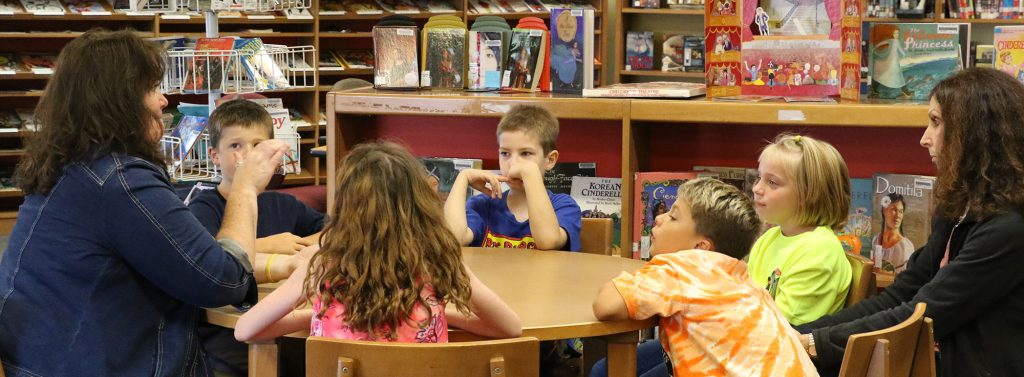 Elementary students sitting at a library table with teacher and educational assistant.