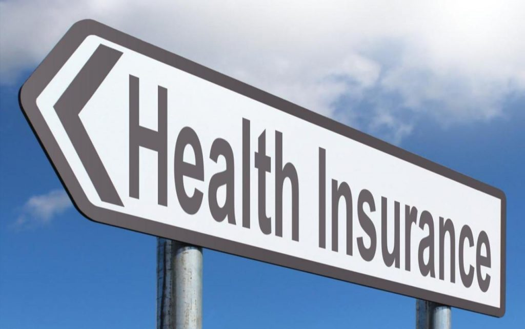 Road sign pointing to the left with the words Health Insurance on it.