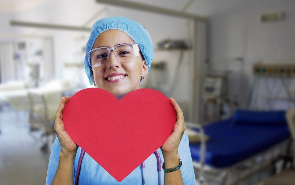 Nurse wearing a hairnet and safety glasses, holding up a red heart in front of her.