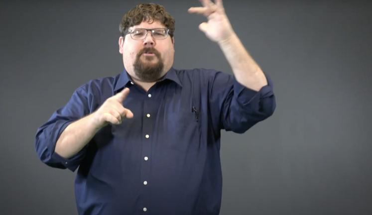 Man with dark hair, glasses, and a goatee wearing a dark blue shirt is using American Sign Language, explaining something to the camera.